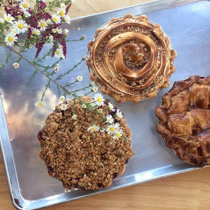 Three decorative pies on a tray.
