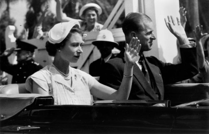 The Queen wearing a half hat and waving from a car.