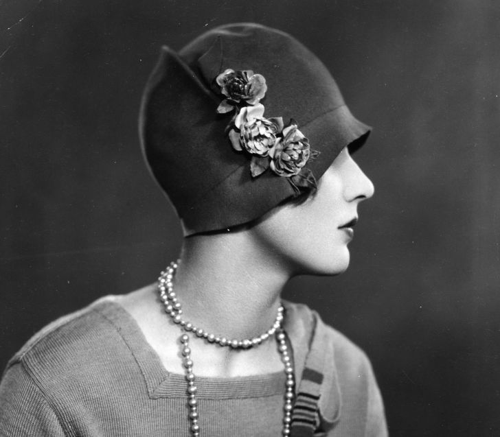 A woman wearing a cloche hat decorated with flowers.