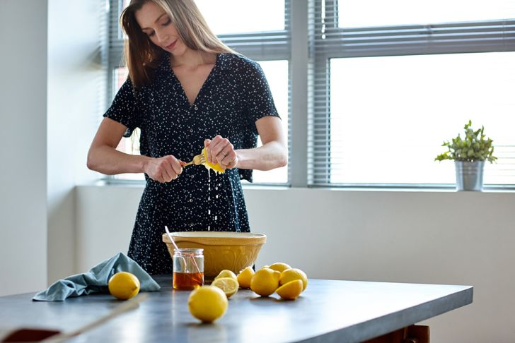 A woman squeezes lemon juice into a bowl.