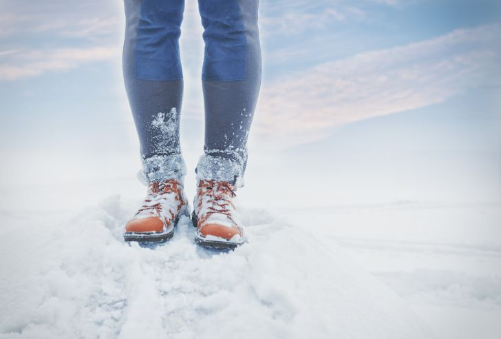 A close-up of a person's legs, feet covered in snow.