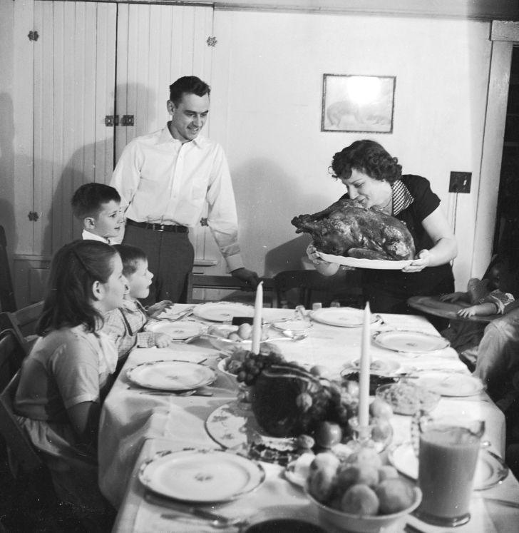 A black and white photo of a family gathering around the table as the mother brings in a turkey.