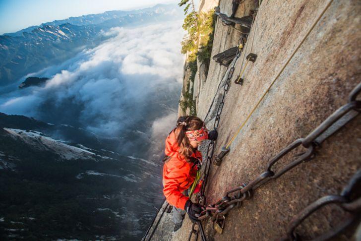 woman climbs mount huashan path
