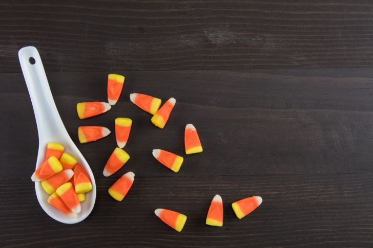 A white spoon full of candy corn.