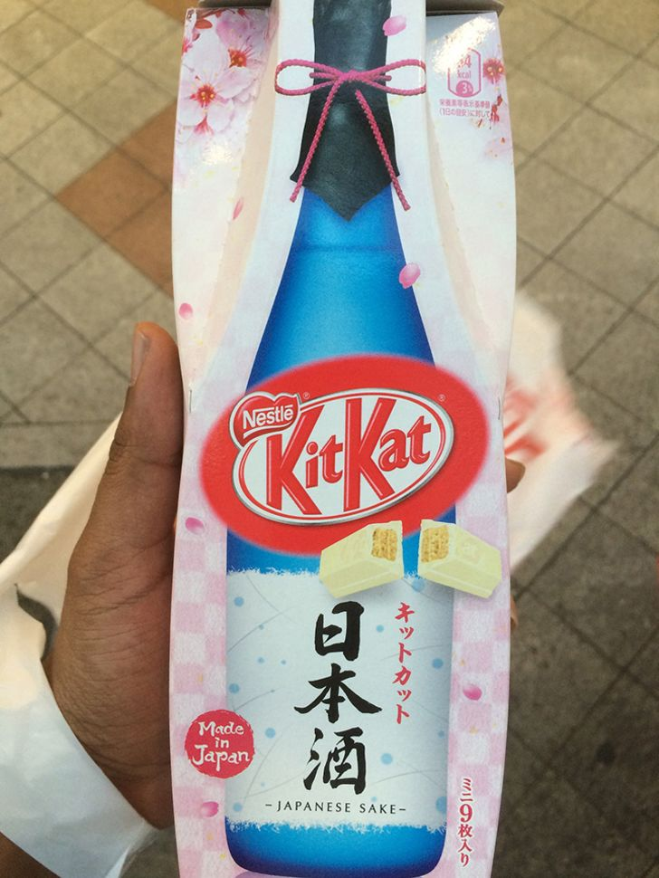A person holding a package of sake-flavored kit kats.
