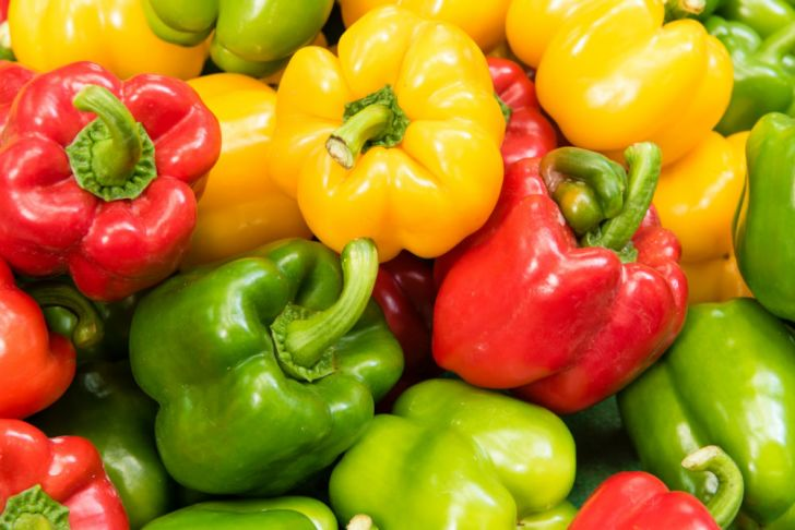 Bell peppers sit in a pile
