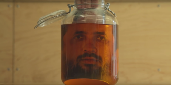A photograph of a face appears in a jar