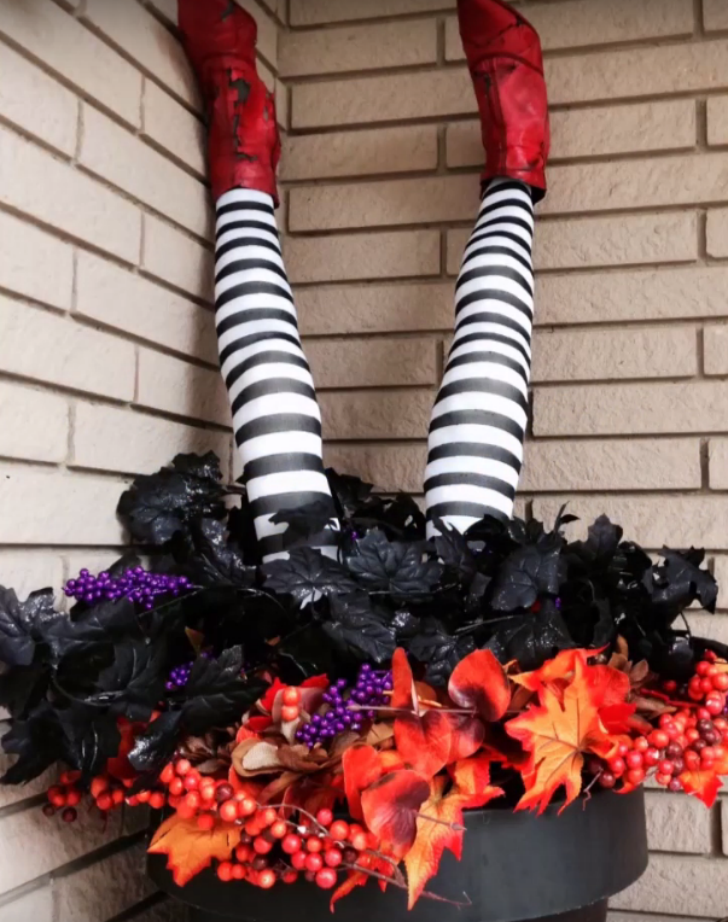 A pair of pool noodle witch legs stick out from a planter