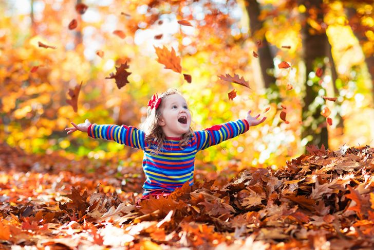 A little girl playing in a pile of autumn leaves