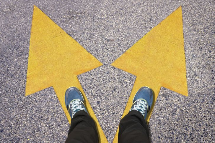 A pair of blue shoes on the ground with yellow arrows pointing in two different directions