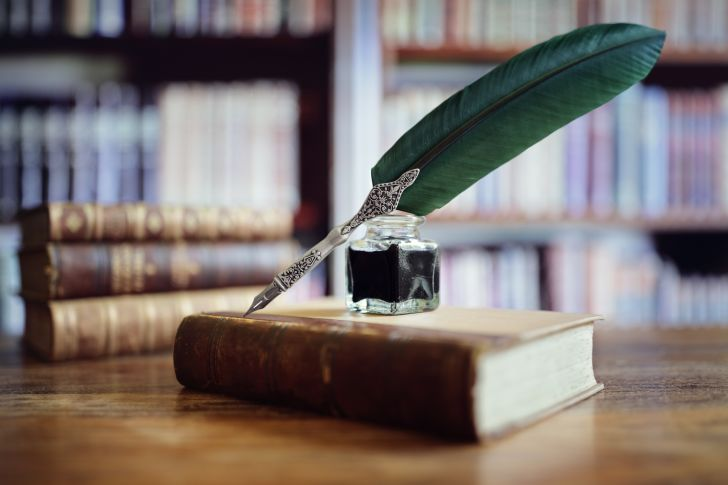 A book of poems on a table with a quill pen and ink pot on top of it.