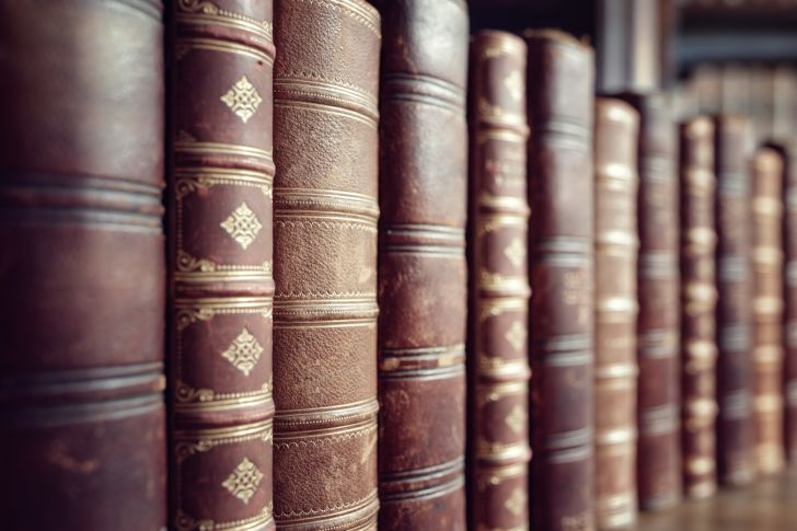 A picture of a book shelf lined with old leather-bound books.