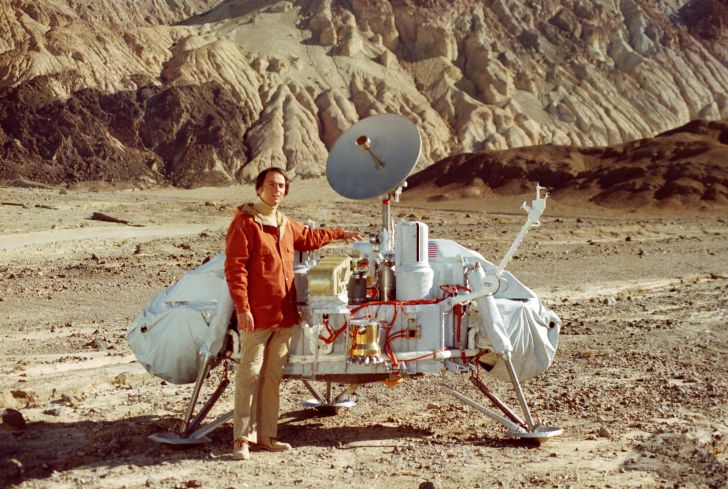 Carl Sagan in a photo with a replica of the Viking lander.
