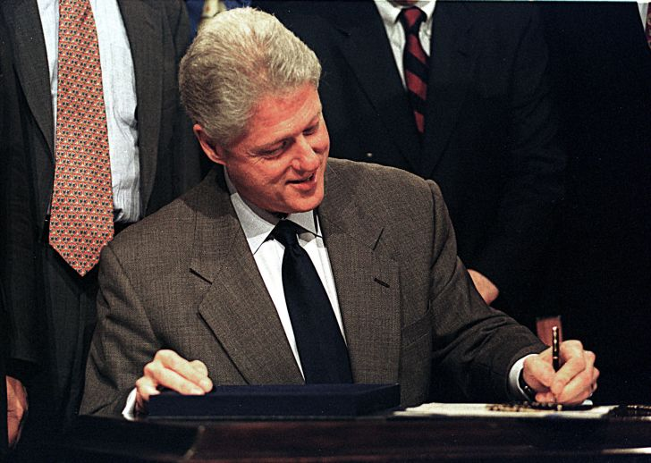 Bill Clinton signing paperwork as President of the United States.