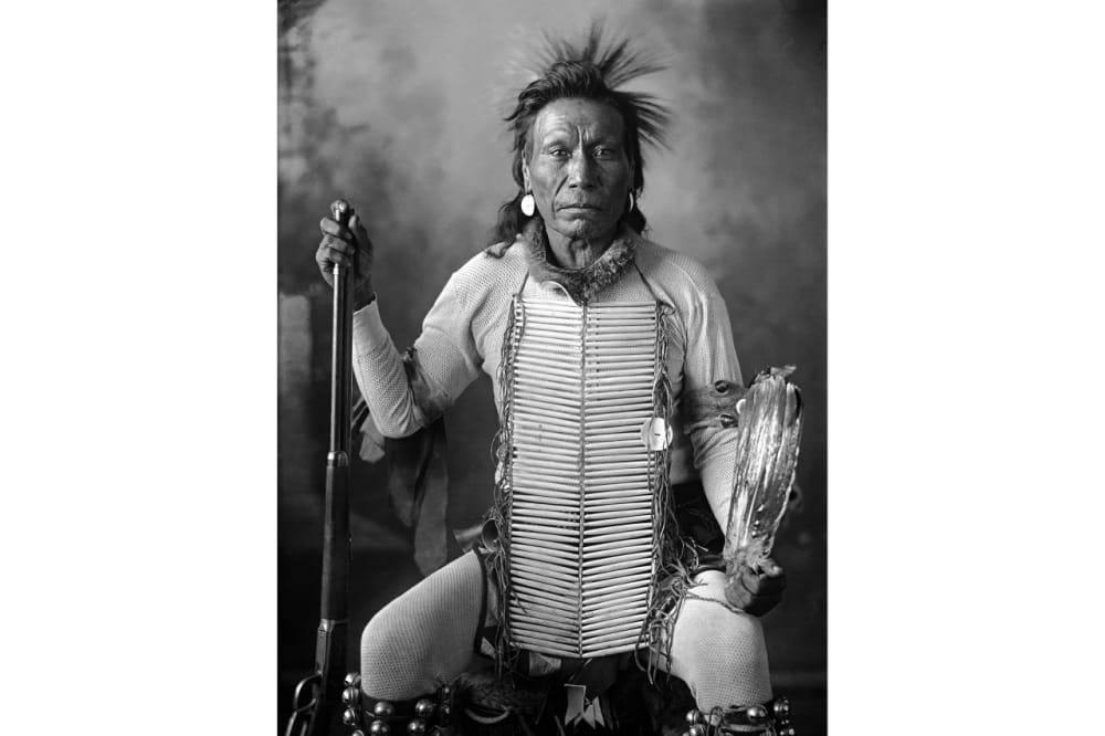 6. A seated man wearing heavily beaded clothing and holding a rifle