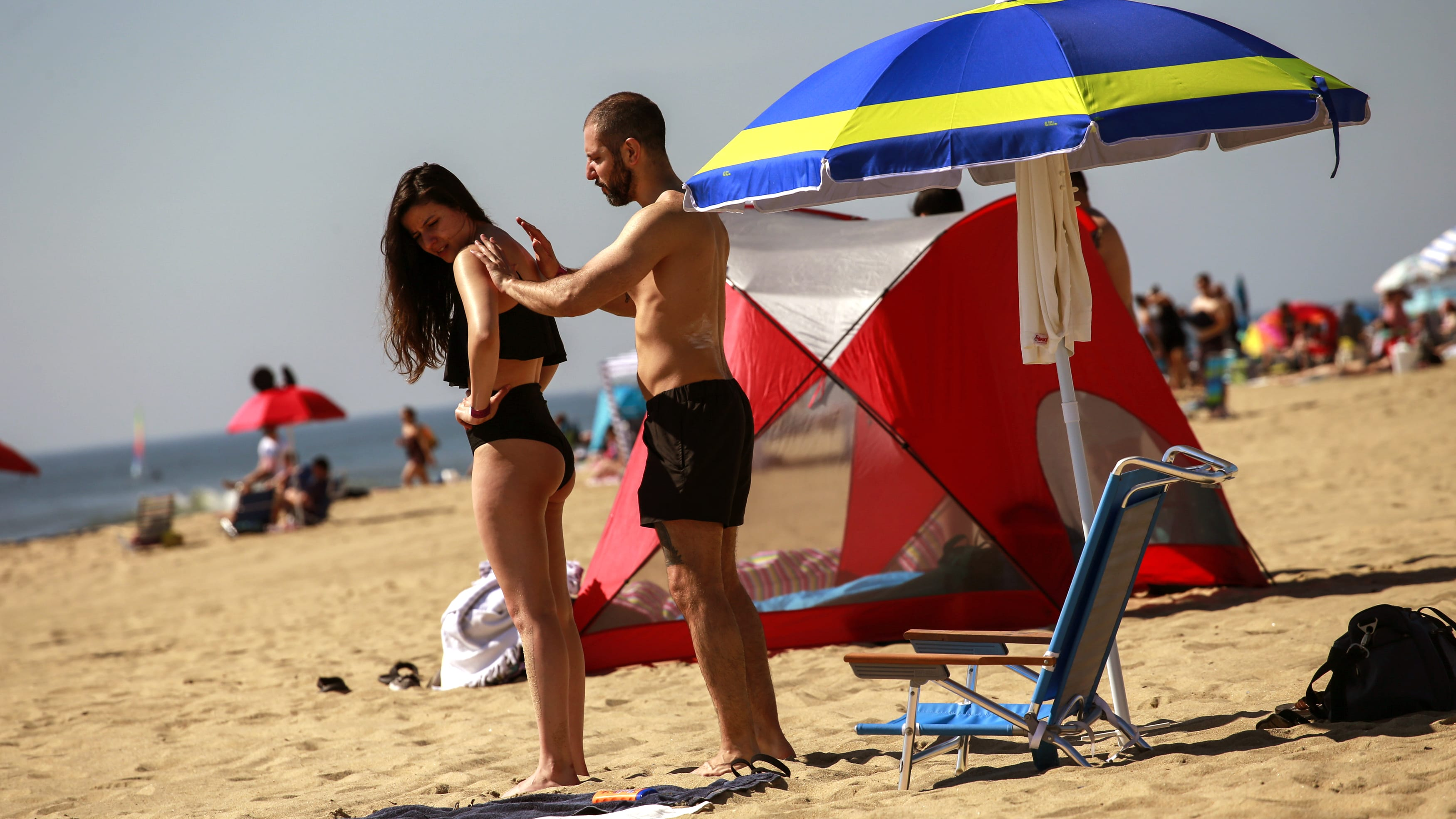 ASBURY PARK, NJ - MAY 26:  A man applies sunscreen to a woman as they visit the beach during Memorial Day weekend on May 26, 2019 in Asbury Park, New Jersey. Memorial Day is the unofficial start of summer and this year New Jersey has banned smoking and vaping on nearly every public beach under tougher new restrictions. (Photo by Kena Betancur/Getty Images)