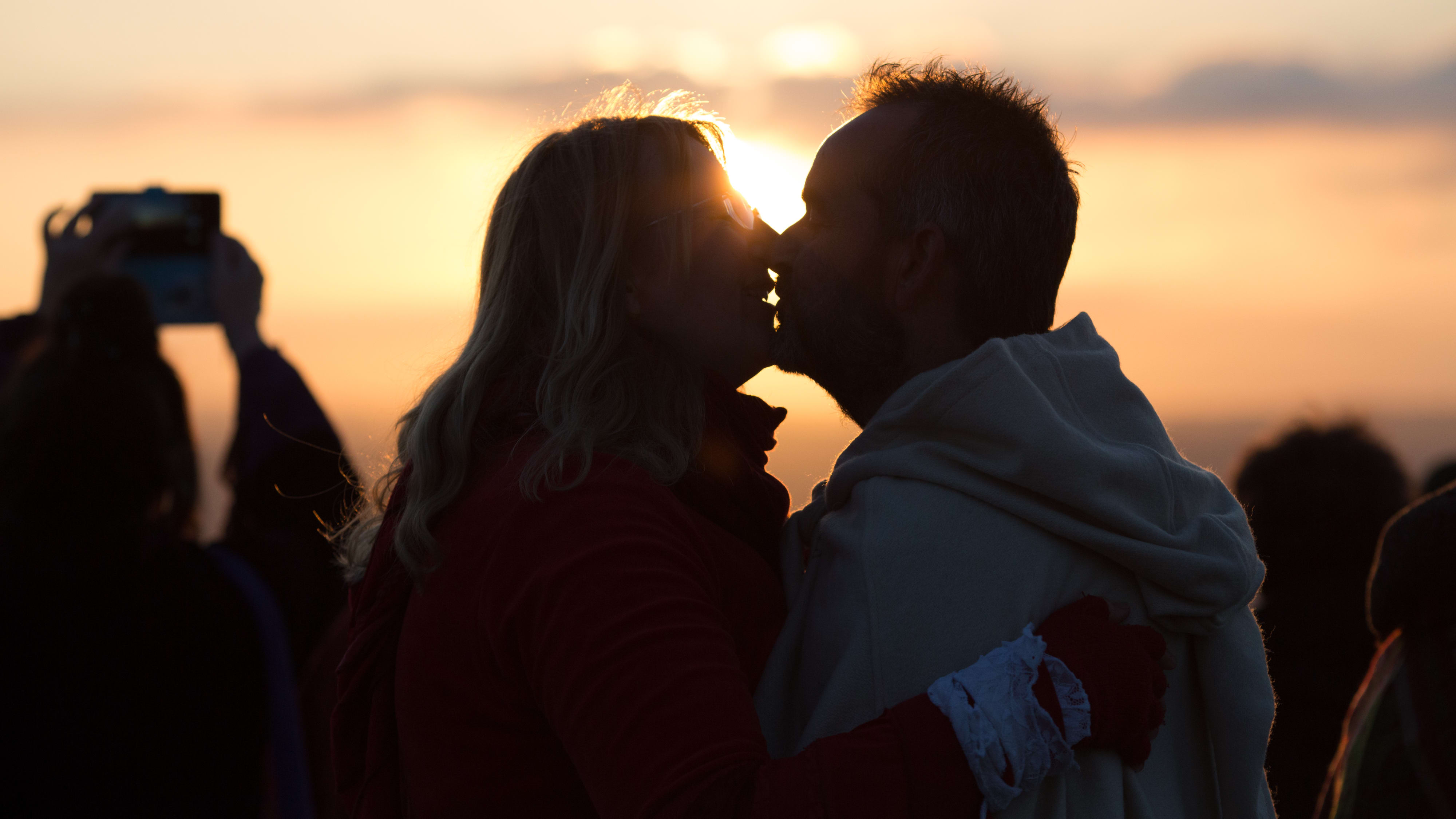 GLASTONBURY, ENGLAND - MAY 01: A couple kiss as people gather on Glastonbury Tor to watch the sun rise as they celebrate Beltane on May 1, 2018 in Somerset, England. Although more synonymous with International Workers' Day, or Labour Day, May Day or Beltane is celebrated by druids and pagans as the beginning of summer and the chance to celebrate the coming of the season of warmth and light. Other traditional English May Day rites and celebrations include Morris dancing and the crowning of a May Queen with celebrations involving a Maypole.  (Photo by Matt Cardy/Getty Images)