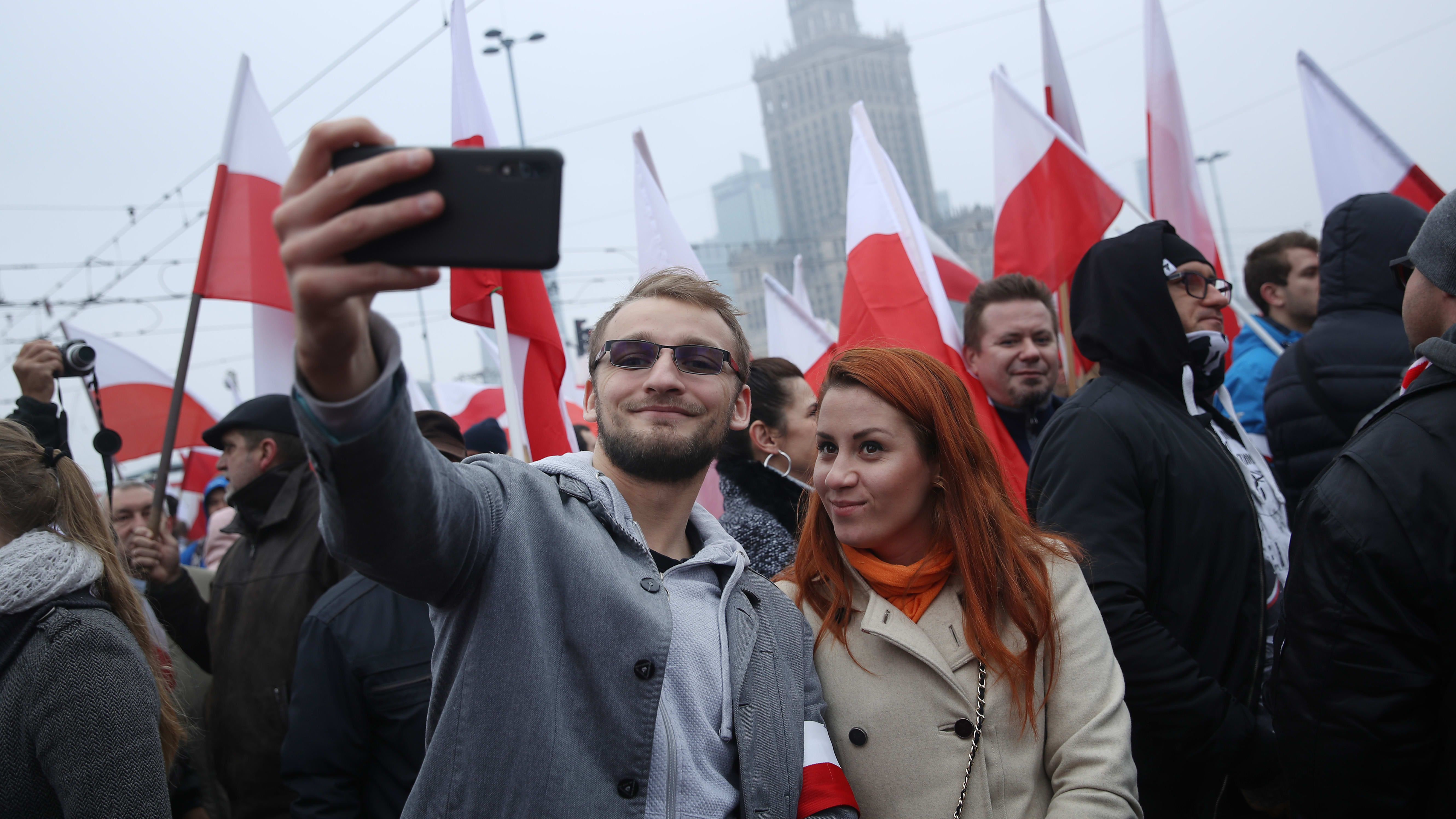 WARSAW, POLAND - NOVEMBER 11: A couple shoots a selfie among people bearing Polish flags prior to the planned March of Independence during events to mark the 100th anniversary of the reinstatement of Polish independence on November 11, 2018 in Warsaw, Poland. Events are taking place throughout the day in the Polish capital today to celebrate the anniversary. The mayor of Warsaw sought to ban the March of Independence, which is at least partially organized by the far-right National Radical Camp, though a court ruled the march may take place.   (Photo by Sean Gallup/Getty Images)