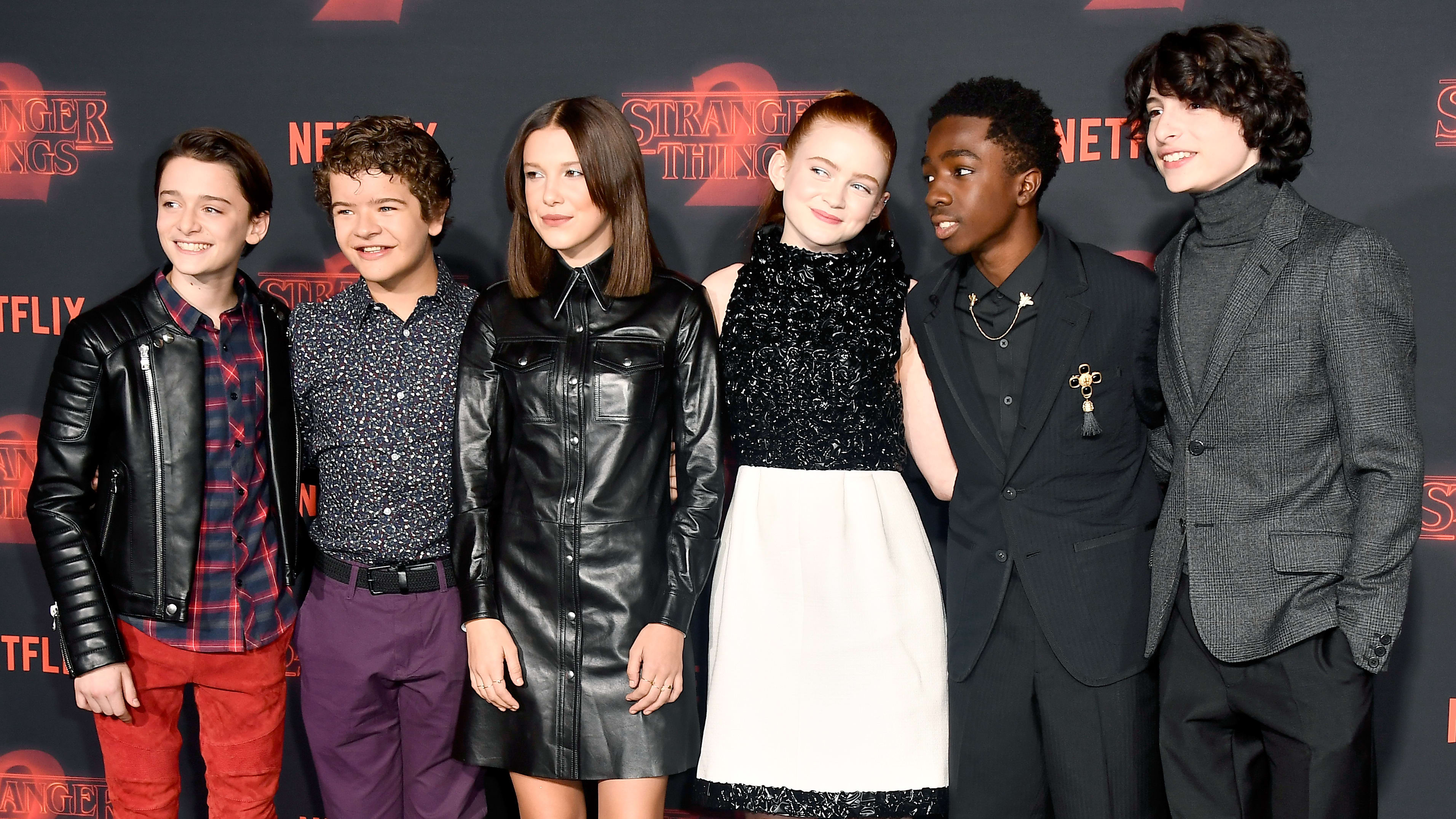 """LOS ANGELES, CA - OCTOBER 26:  (L-R) Noah Schnapp, Gaten Matarazzo, Millie Bobby Brown, Sadie Sink, Caleb McLaughlin, and Finn Wolfhard attend the premiere of Netflix's """"Stranger Things"""" Season 2 at Regency Bruin Theatre on October 26, 2017 in Los Angeles, California.  (Photo by Frazer Harrison/Getty Images)"""