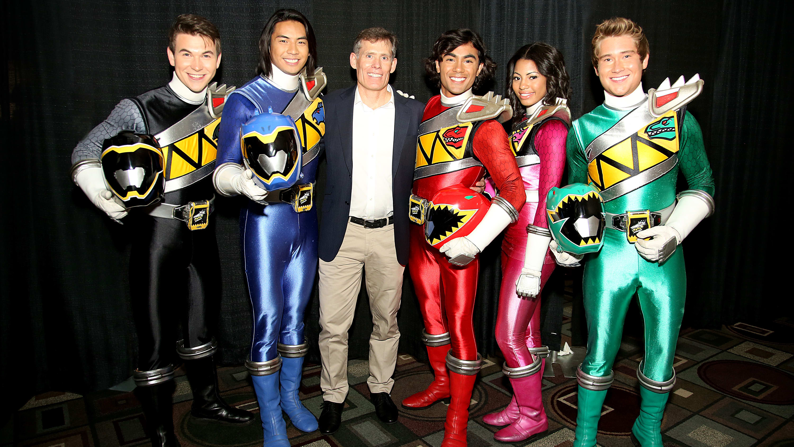 PASADENA, CA - AUGUST 23: (L-R) The new cast of Power Rangers Dino Charge, including James Davies (Black Dino Charge Ranger), Yoshi Sudarso (Blue Dino Charge Ranger), Brennan Mejia (Red Dino Charge Ranger), Camille Manning Hyde (Pink Dino Charge Ranger) and Michael Taber (Green Dino Charge Ranger) pose with Executive Producer Chip Lynn at the 4th bi-annual Power Morphicon Convention in Pasadena, CA. (Photo by Rachel Murray/Getty Images for Saban Brands)