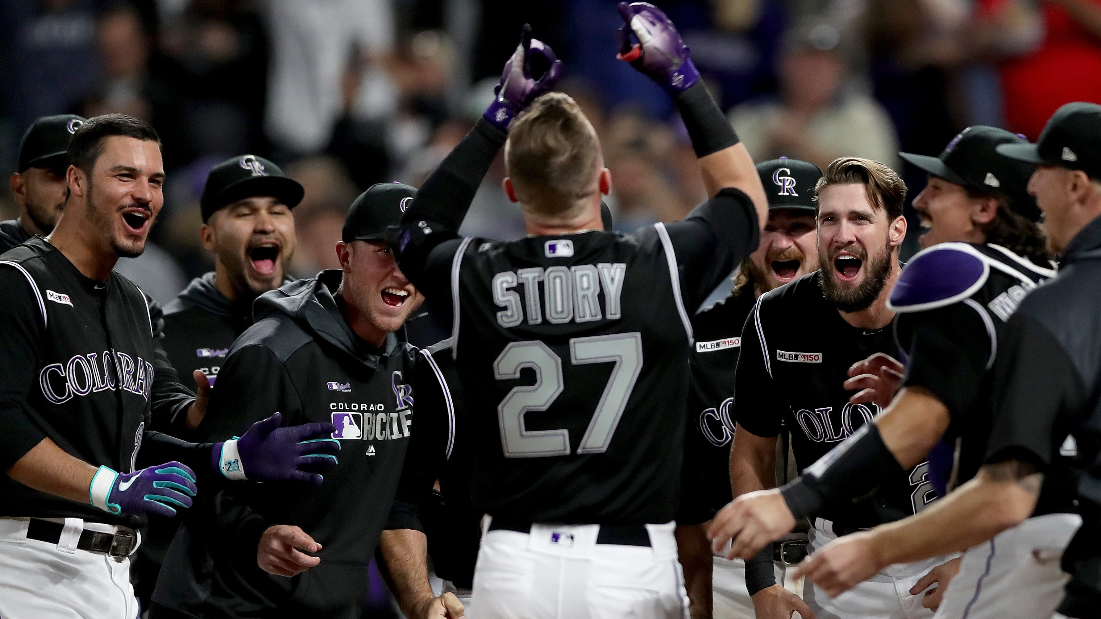 DENVER, COLORADO - MAY 24: Trevor Story #27 of the Colorado Rockies is met at the plate by his teammates after hitting a 2 RBI walk off home run in the ninth inning against the Baltimore Orioles at Coors Field on May 24, 2019 in Denver, Colorado. (Photo by Matthew Stockman/Getty Images)