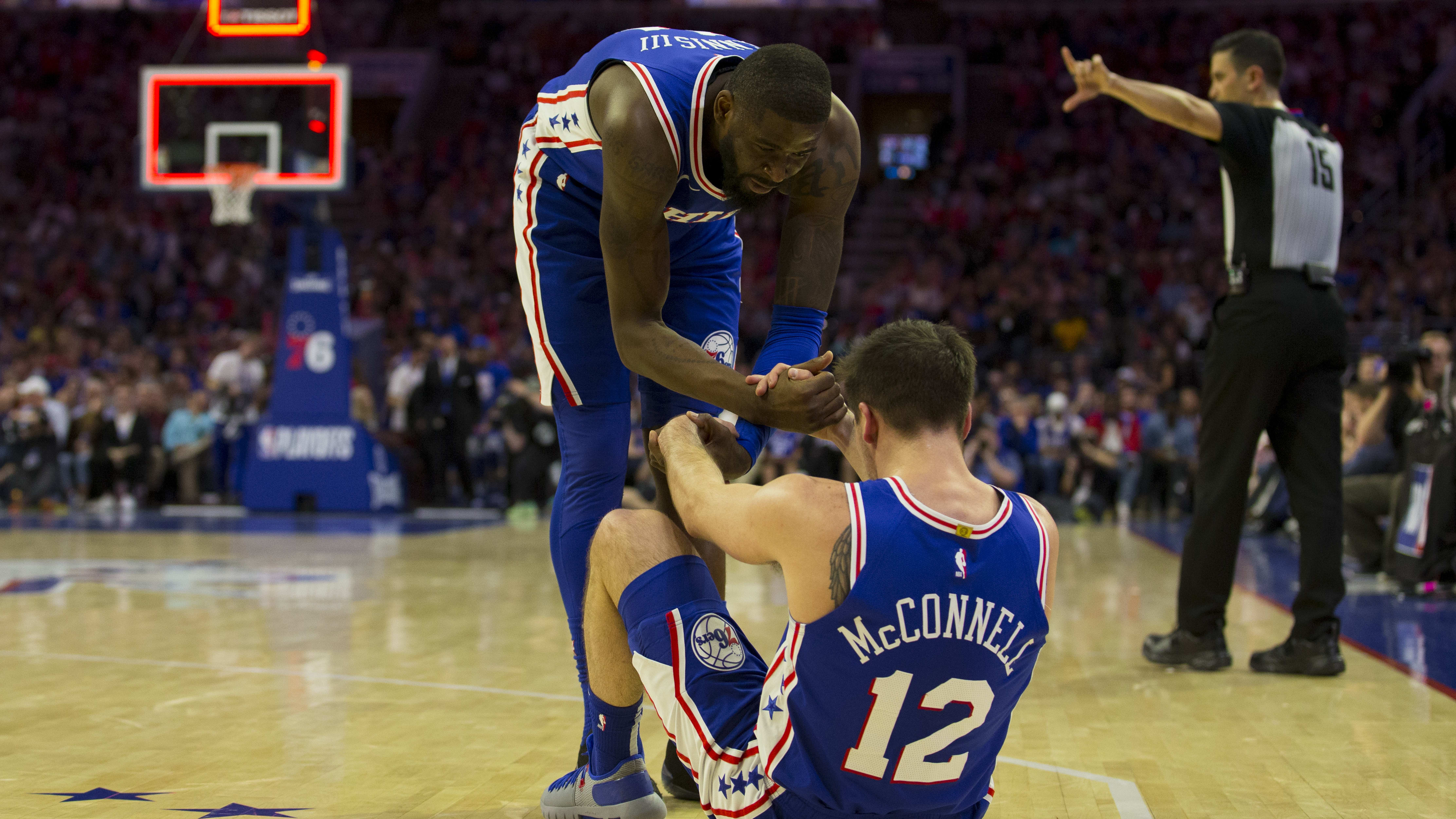 PHILADELPHIA, PA - APRIL 23: James Ennis III #11 of the Philadelphia 76ers helps T.J. McConnell #12 off the floor against the Brooklyn Nets in Game Five of Round One of the 2019 NBA Playoffs at the Wells Fargo Center on April 23, 2019 in Philadelphia, Pennsylvania. NOTE TO USER: User expressly acknowledges and agrees that, by downloading and or using this photograph, User is consenting to the terms and conditions of the Getty Images License Agreement. (Photo by Mitchell Leff/Getty Images)