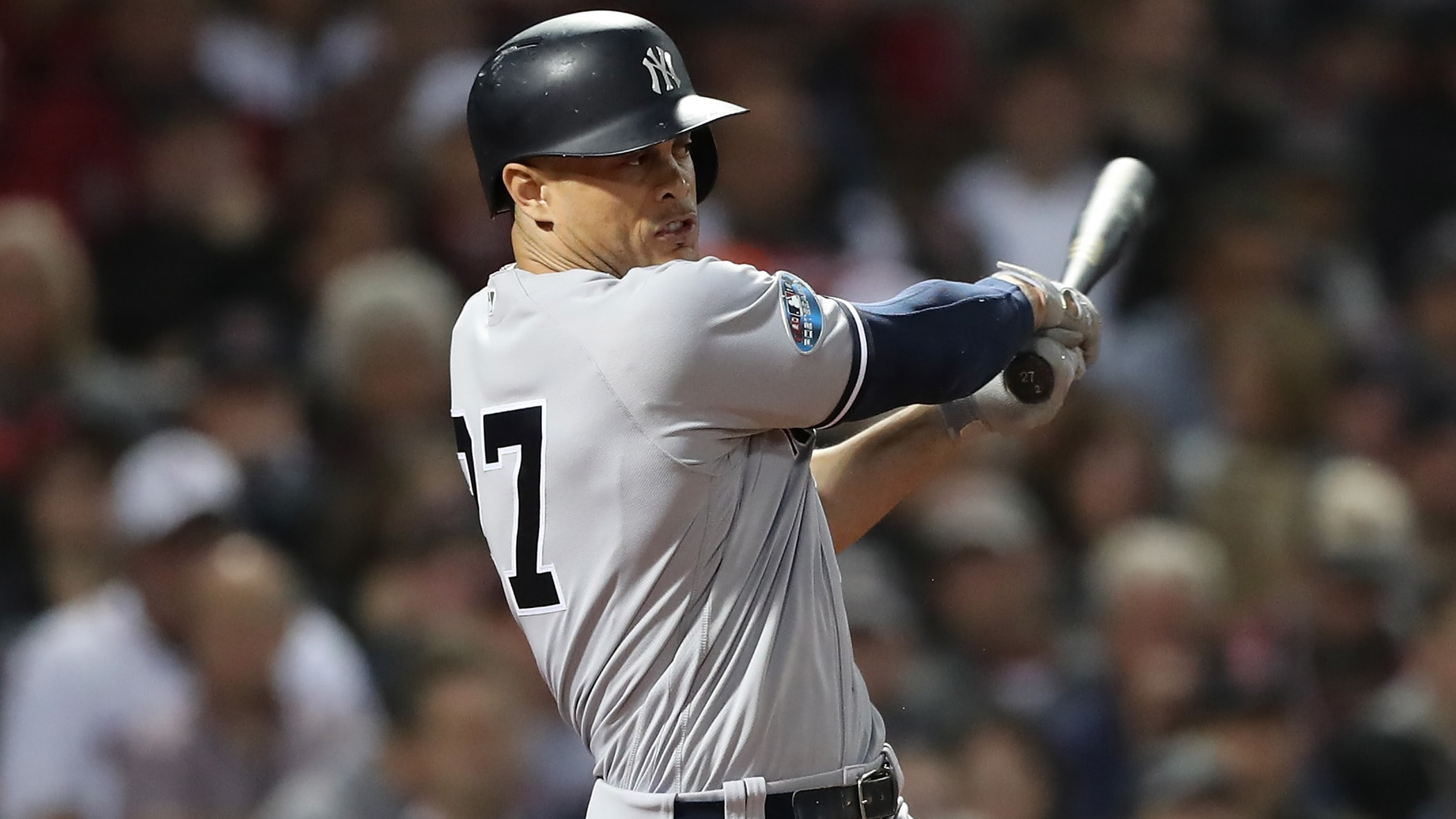 BOSTON, MA - OCTOBER 06:  Giancarlo Stanton #27 of the New York Yankees hits an infield single during the seventh inning of Game Two of the American League Division Series against the Boston Red Sox at Fenway Park on October 6, 2018 in Boston, Massachusetts.  (Photo by Elsa/Getty Images)