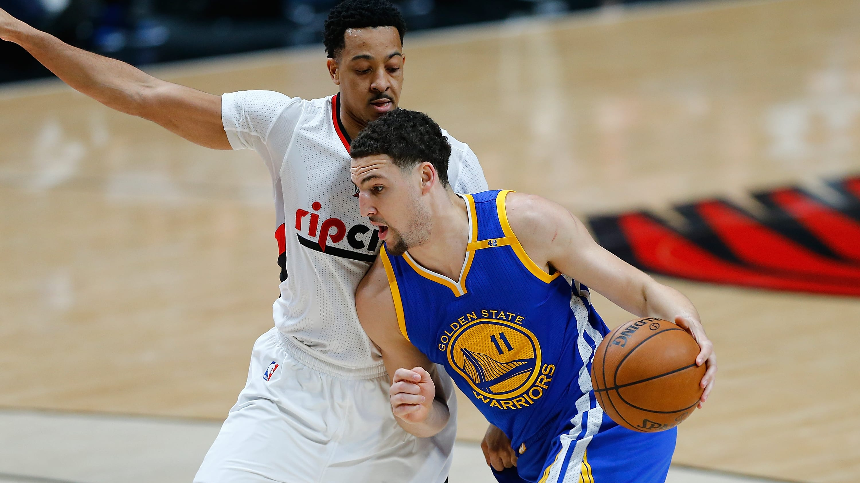 PORTLAND, OR - APRIL 24:  Klay Thompson #11 of the Golden State Warriors drives against CJ McCollum #3 of the Portland Trail Blazers during Game Four of the Western Conference Quarterfinals of  the 2017 NBA Playoffs at Moda Center on April 24, 2017 in Portland, Oregon.  NOTE TO USER: User expressly acknowledges and agrees that, by downloading and or using this photograph, User is consenting to the terms and conditions of the Getty Images License Agreement.  (Photo by Jonathan Ferrey/Getty Images)
