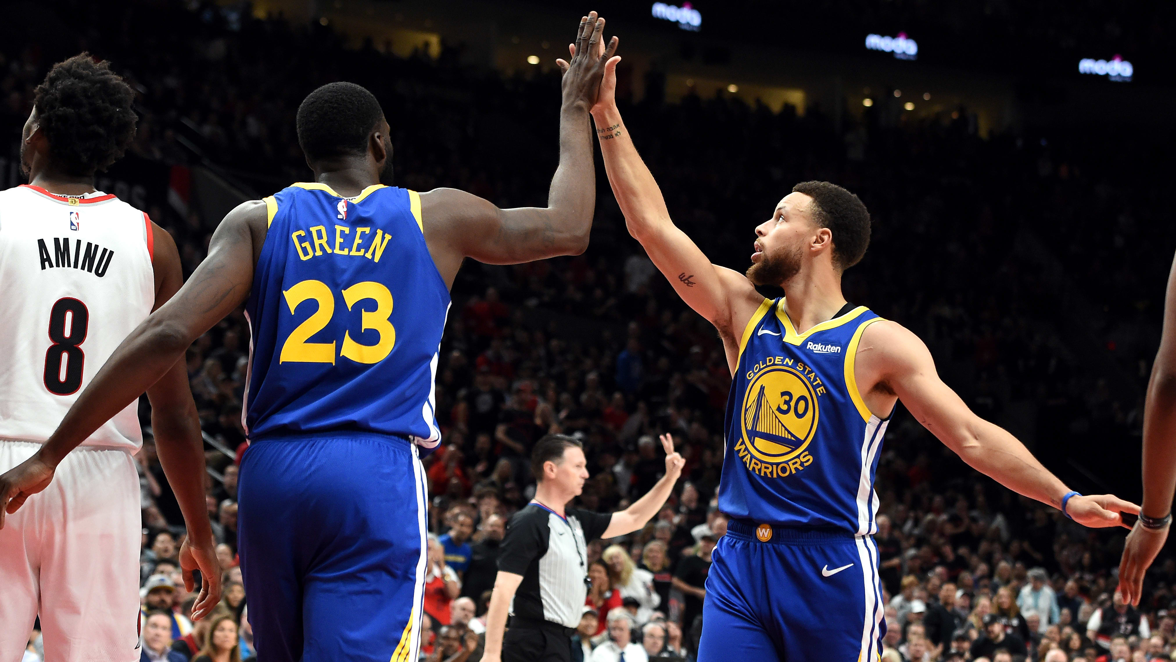 PORTLAND, OREGON - MAY 18: Stephen Curry #30 of the Golden State Warriors high fives Draymond Green #23 during the first half against the Portland Trail Blazers in game three of the NBA Western Conference Finals at Moda Center on May 18, 2019 in Portland, Oregon. NOTE TO USER: User expressly acknowledges and agrees that, by downloading and or using this photograph, User is consenting to the terms and conditions of the Getty Images License Agreement. (Photo by Steve Dykes/Getty Images)