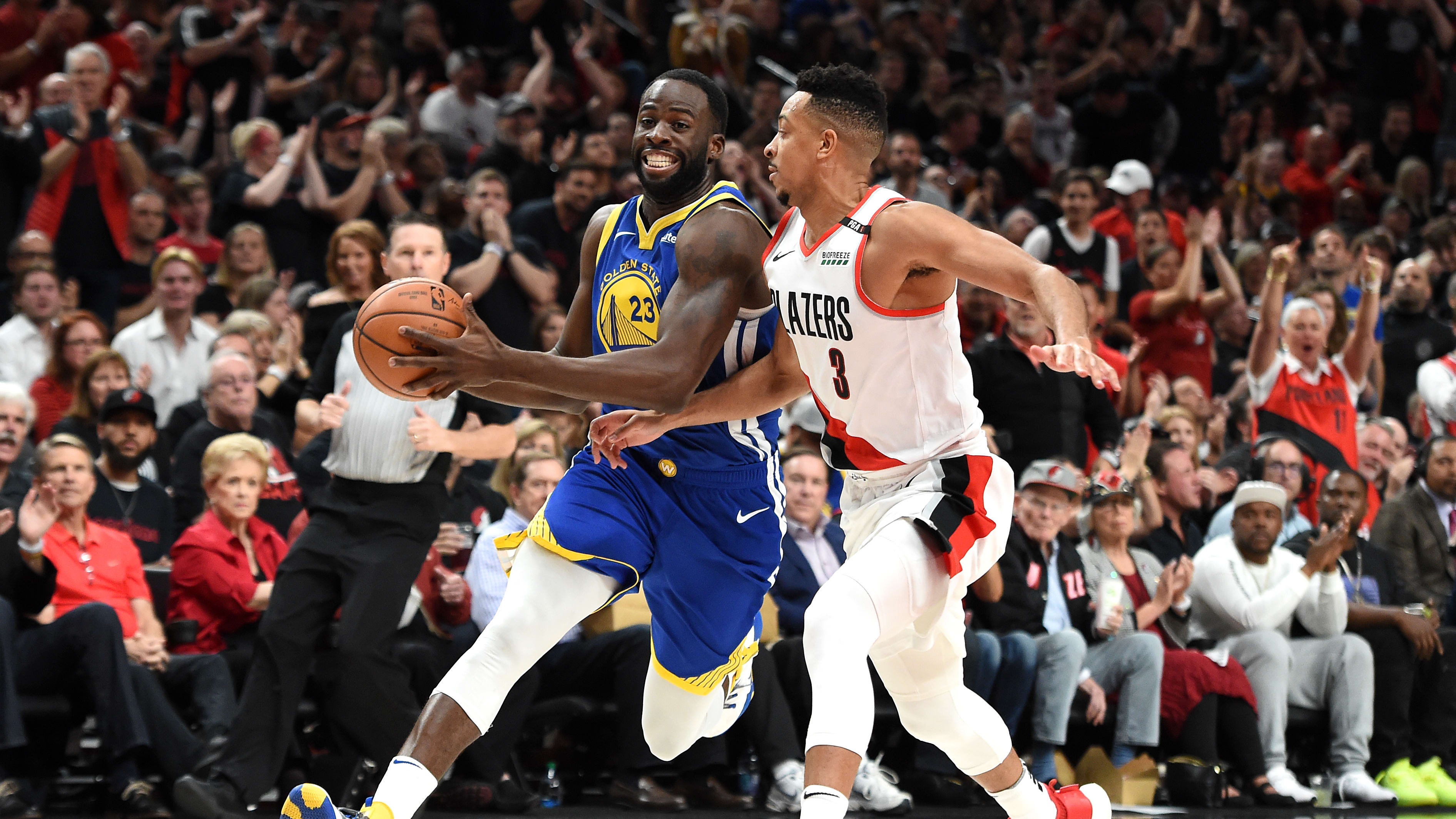 PORTLAND, OREGON - MAY 18: Draymond Green #23 of the Golden State Warriors drives to the basket against CJ McCollum #3 of the Portland Trail Blazers in game three of the NBA Western Conference Finals at Moda Center on May 18, 2019 in Portland, Oregon. NOTE TO USER: User expressly acknowledges and agrees that, by downloading and or using this photograph, User is consenting to the terms and conditions of the Getty Images License Agreement. (Photo by Steve Dykes/Getty Images)