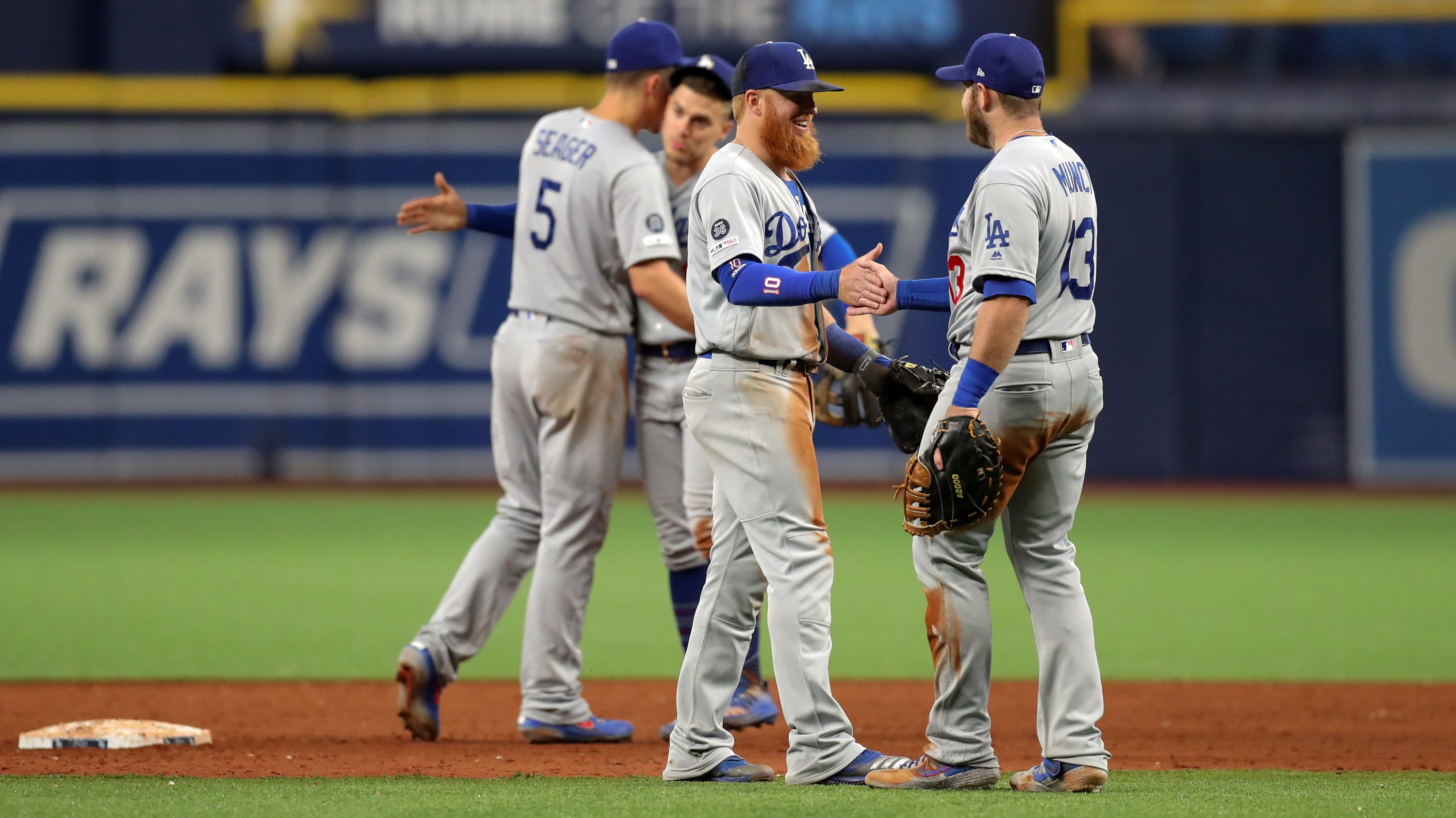 ST. PETERSBURG, FL - MAY 21:  Corey Seager #5, Justin Turner #10 and Max Muncy #13 of the Los Angeles Dodgers celebrate a win over the Tampa Bay Rays at Tropicana Field on May 21, 2019 in St. Petersburg, Florida. (Photo by Mike Carlson/Getty Images)