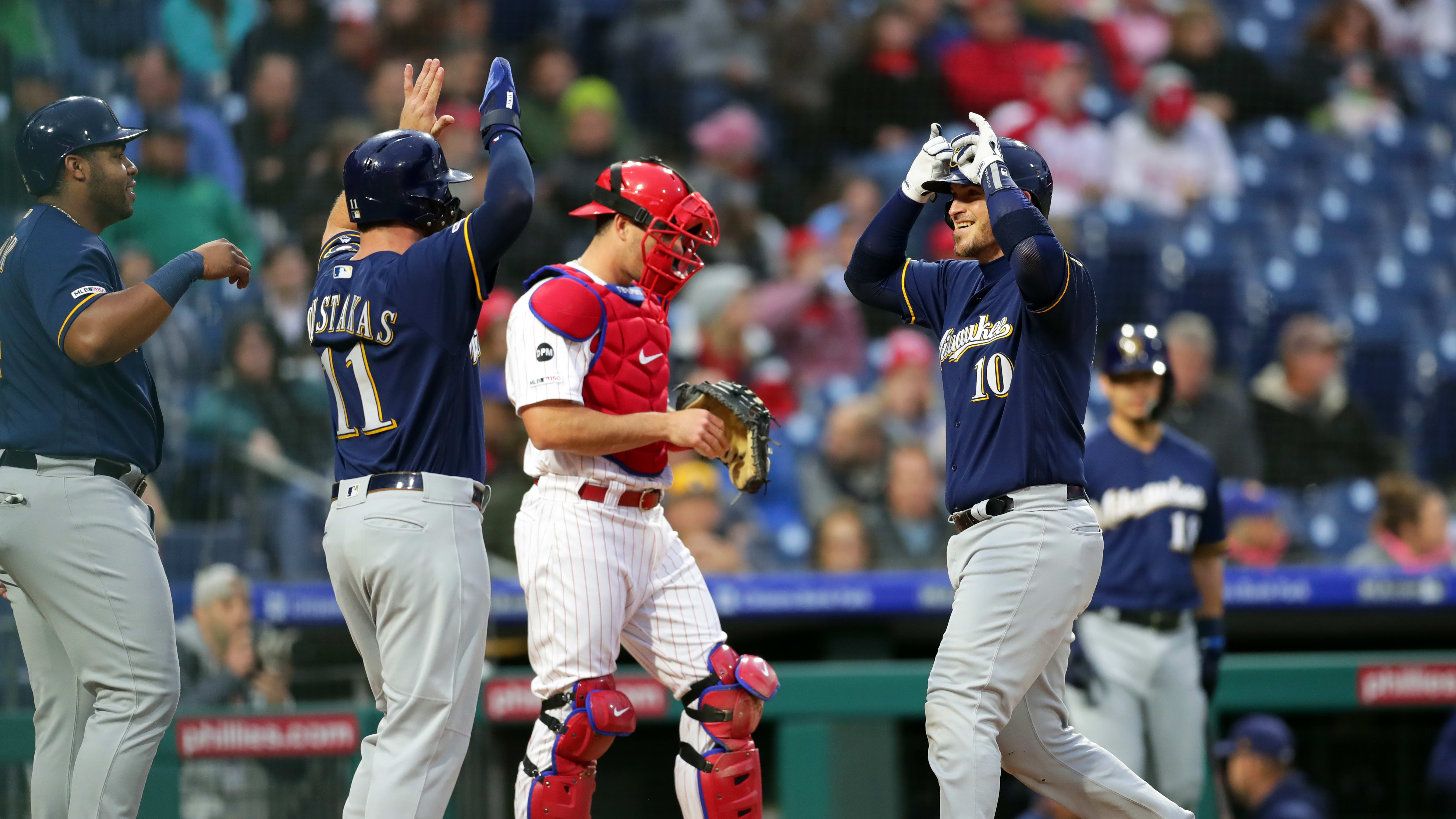 PHILADELPHIA, PA - MAY 14: Yasmani Grandal #10 of the Milwaukee Brewers is greeted at home plate by Mike Moustakas #11 and Jesus Aguilar #24 after hitting a three-run home run in the second inning during a game against the Philadelphia Phillies at Citizens Bank Park on May 14, 2019 in Philadelphia, Pennsylvania. (Photo by Hunter Martin/Getty Images)
