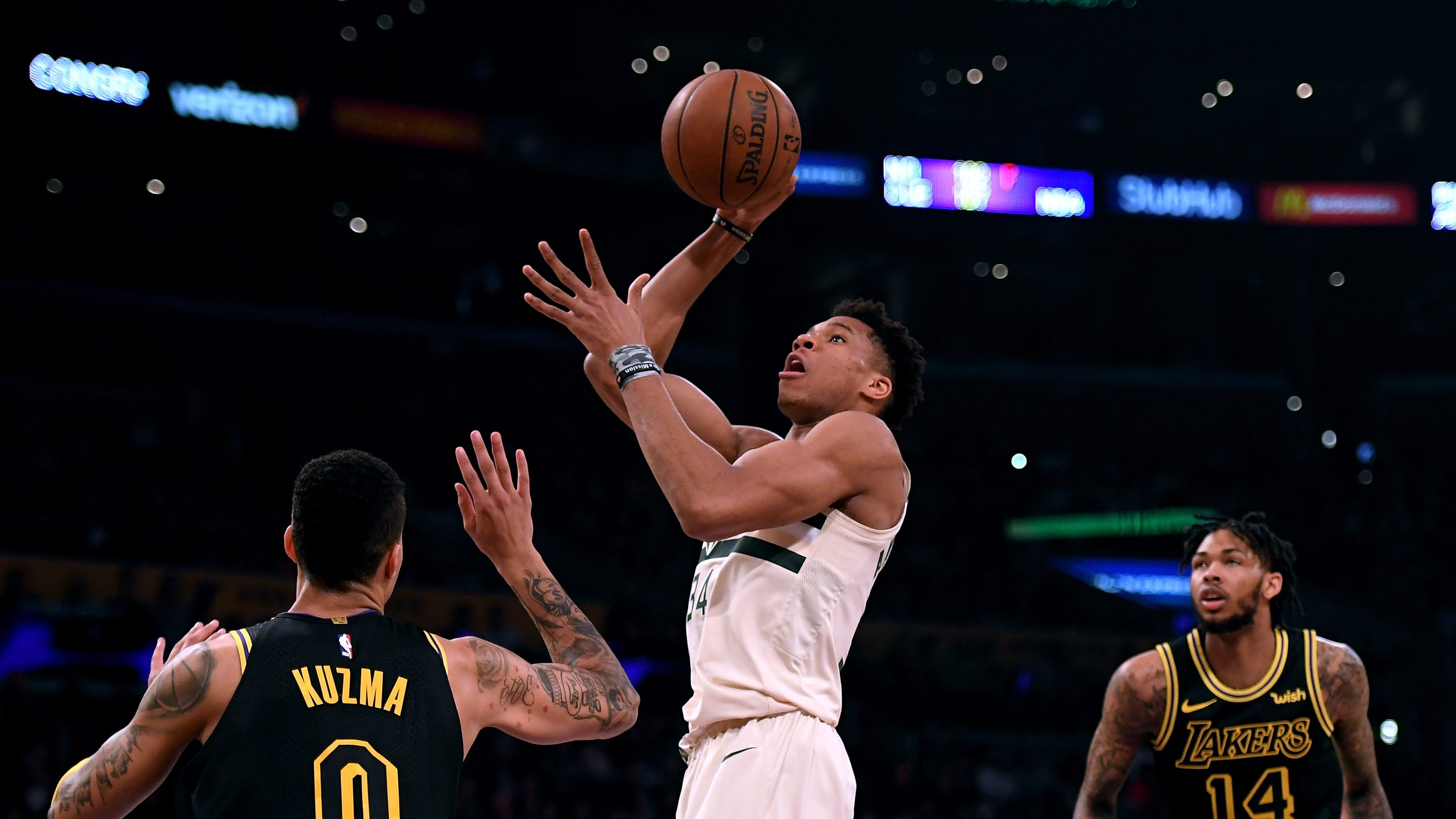LOS ANGELES, CA - MARCH 30:  Giannis Antetokounmpo #34 of the Milwaukee Bucks scores on a shot between Kyle Kuzma #0 and Brandon Ingram #14 of the Los Angeles Lakers during the first half at Staples Center on March 30, 2018 in Los Angeles, California.  (Photo by Harry How/Getty Images)