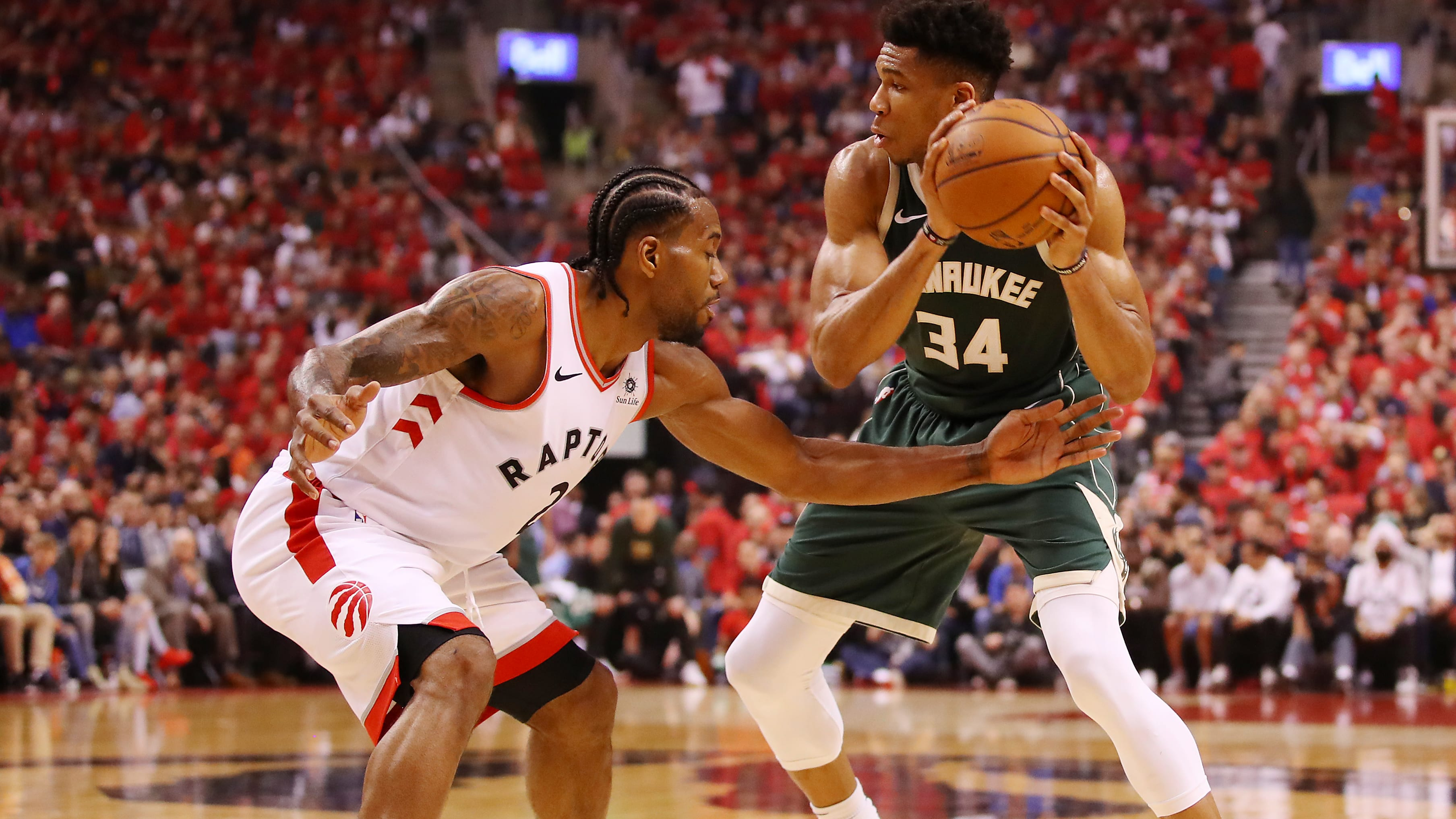 TORONTO, ONTARIO - MAY 19: Giannis Antetokounmpo #34 of the Milwaukee Bucks handles the ball against Kawhi Leonard #2 of the Toronto Raptors during the first half in game three of the NBA Eastern Conference Finals at Scotiabank Arena on May 19, 2019 in Toronto, Canada. NOTE TO USER: User expressly acknowledges and agrees that, by downloading and or using this photograph, User is consenting to the terms and conditions of the Getty Images License Agreement. (Photo by Gregory Shamus/Getty Images)