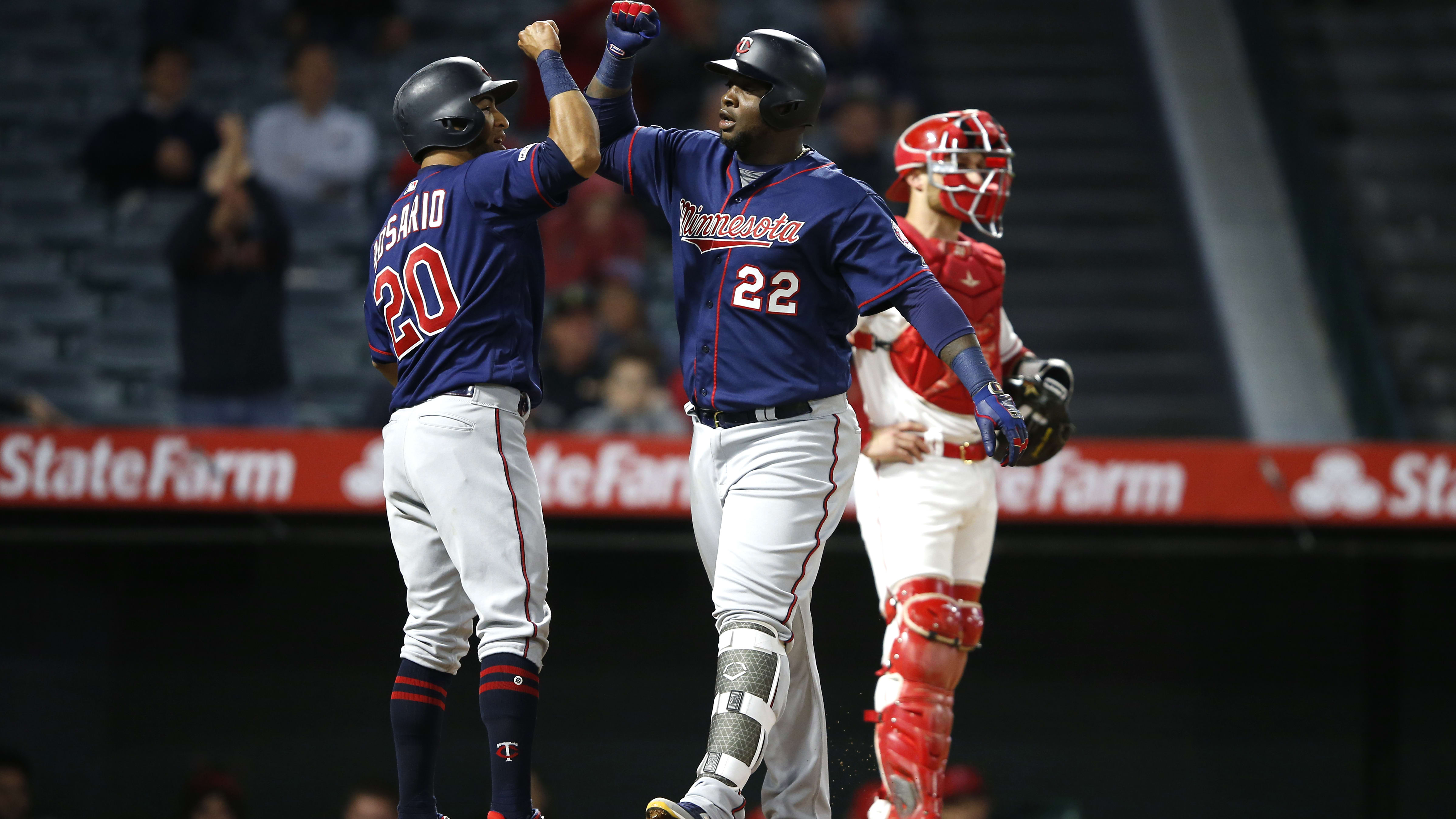 ANAHEIM, CALIFORNIA - MAY 20:  Eddie Rosario #20 of the Minnesota Twins congratulates Miguel Sano #22 of the Minnesota Twins  after his three-run homerun as Jonathan Lucroy #20 of the Los Angeles Angels of Anaheim looks on during the eighth inning of a game at Angel Stadium of Anaheim on May 20, 2019 in Anaheim, California. (Photo by Sean M. Haffey/Getty Images)
