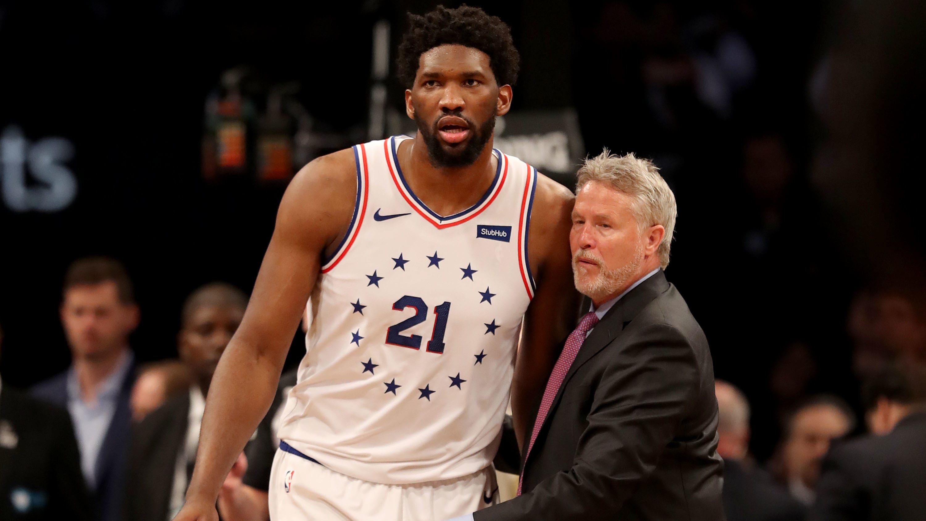 NEW YORK, NEW YORK - APRIL 20:  Head coach Brett Brown of the Philadelphia 76ers holds back his player Joel Embiid #21 after a scuffle between Brooklyn Nets and Philadelphia 76ers players in the third quarter at Barclays Center on April 20, 2019 in the Brooklyn borough of New York City.The Philadelphia 76ers defeated the Brooklyn Nets 112-108. NOTE TO USER: User expressly acknowledges and agrees that, by downloading and or using this photograph, User is consenting to the terms and conditions of the Getty Images License Agreement. (Photo by Elsa/Getty Images)
