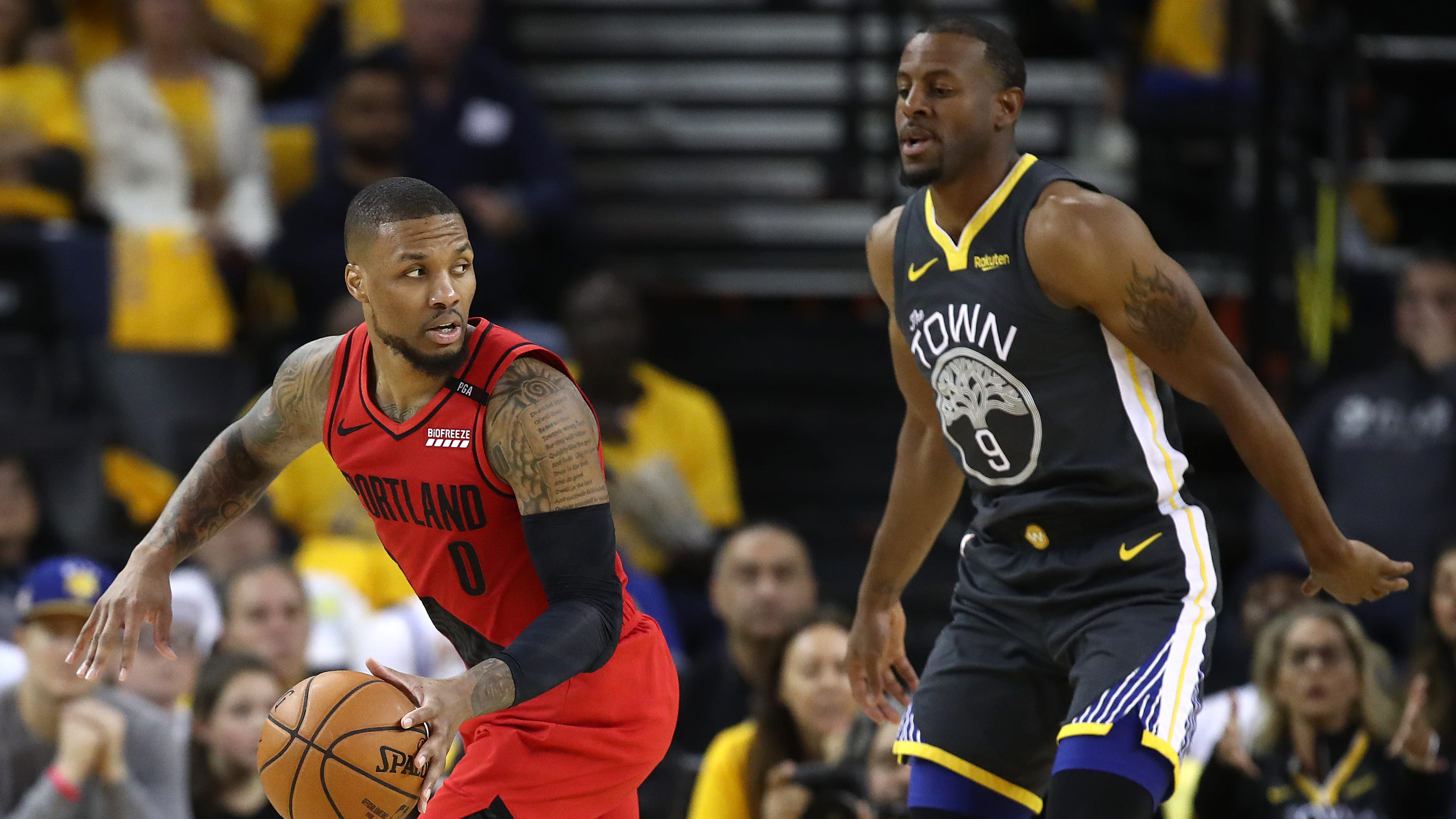 OAKLAND, CALIFORNIA - MAY 16: Damian Lillard #0 of the Portland Trail Blazers controls the ball against Andre Iguodala #9 of the Golden State Warriors in game two of the NBA Western Conference Finals at ORACLE Arena on May 16, 2019 in Oakland, California. NOTE TO USER: User expressly acknowledges and agrees that, by downloading and or using this photograph, User is consenting to the terms and conditions of the Getty Images License Agreement. (Photo by Ezra Shaw/Getty Images)
