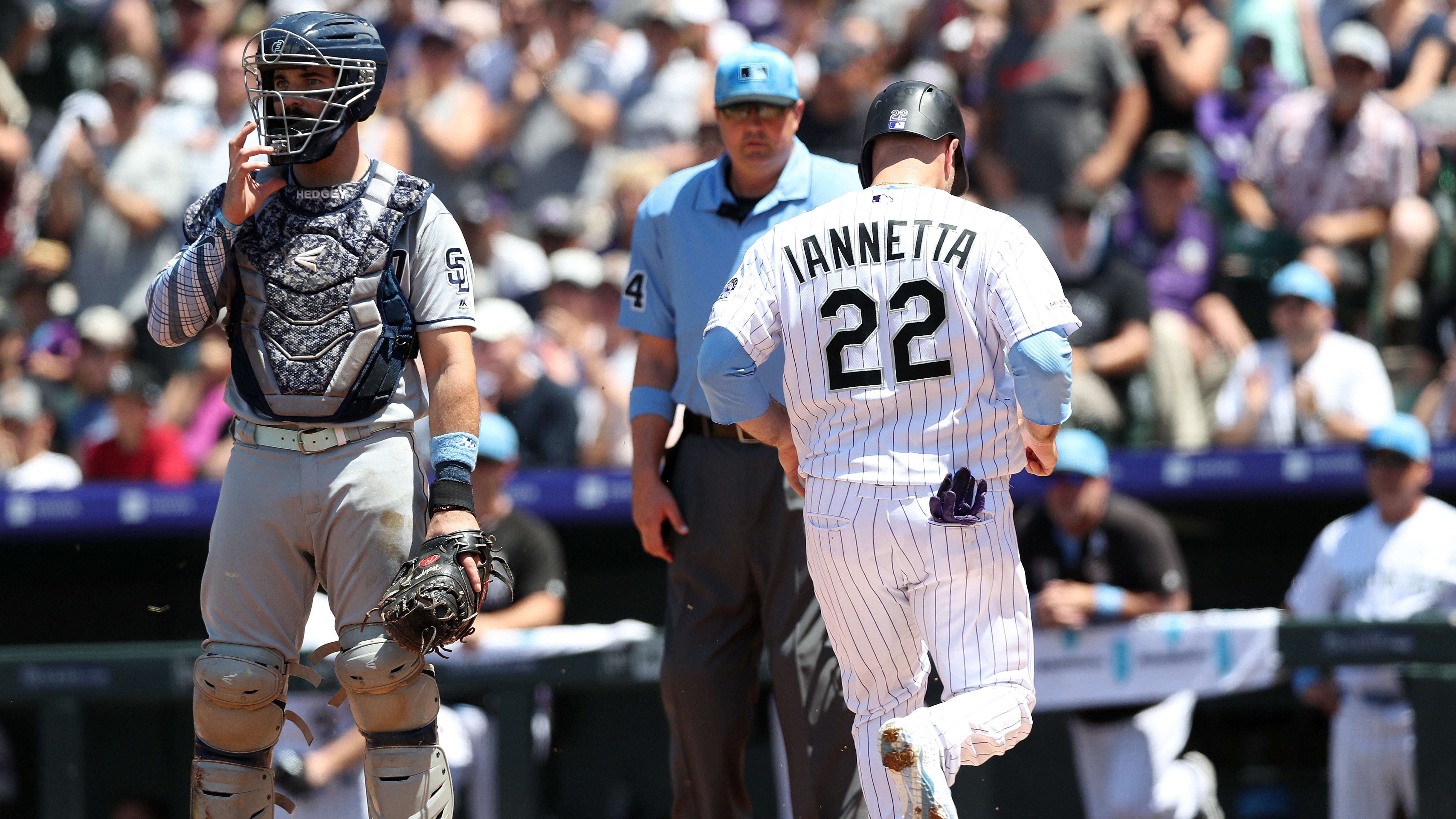 DENVER, COLORADO - JUNE 16:  Chris Iannetta #22 of the Colorado Rockies scores on a fielding error on a hit by Charlie Blackmon in the first inning against the San Diego Padres at Coors Field on June 16, 2019 in Denver, Colorado. (Photo by Matthew Stockman/Getty Images)
