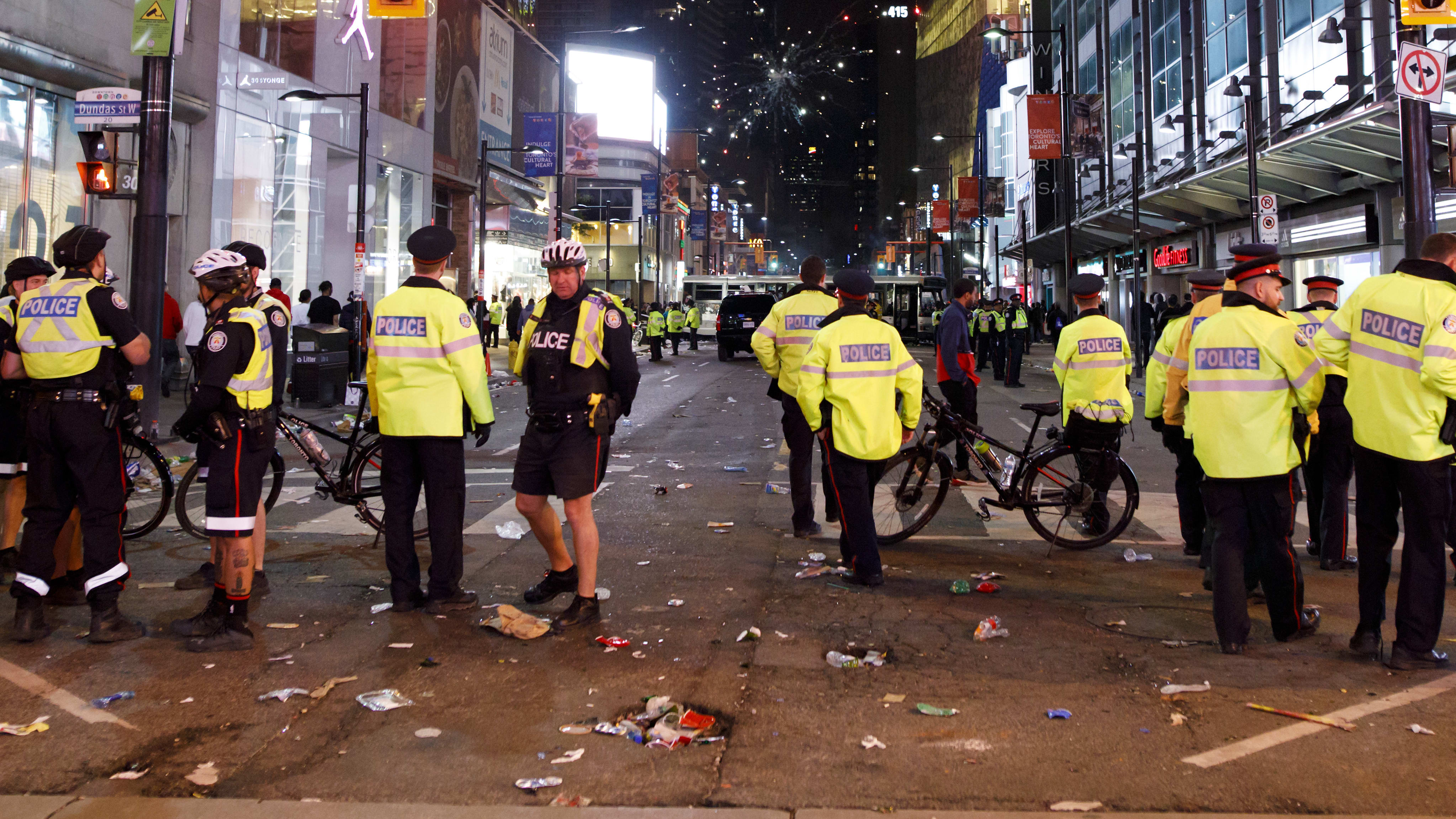TORONTO, ON - JUNE 14:  Fireworks are seen beyond a line of Toronto Police officers amidst celebrations on Yonge St. after the Toronto Raptors beat the Golden State Warriors in Game Six of the NBA Finals, on June 14, 2019 in Toronto, Canada. (Photo by Cole Burston/Getty Images)